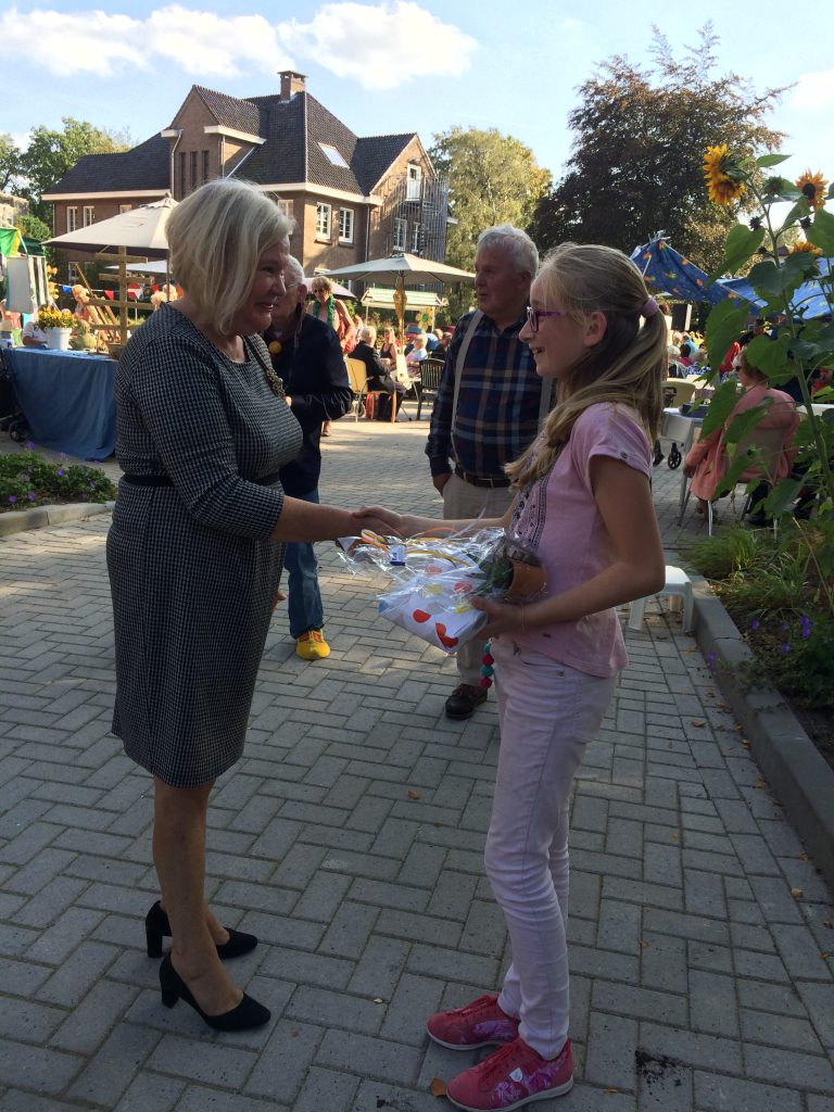 Gerdi Dorpmans (bewoner) en Eline (buurmeisje en vrijwilliger) hebben de fruitbomen ontvangen.